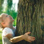 Mädchen umarmt Baum.